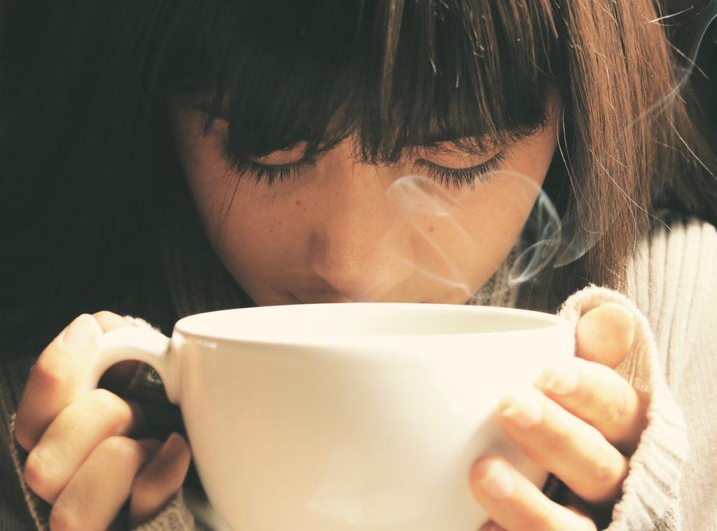 暖かい飲み物で安心する女性