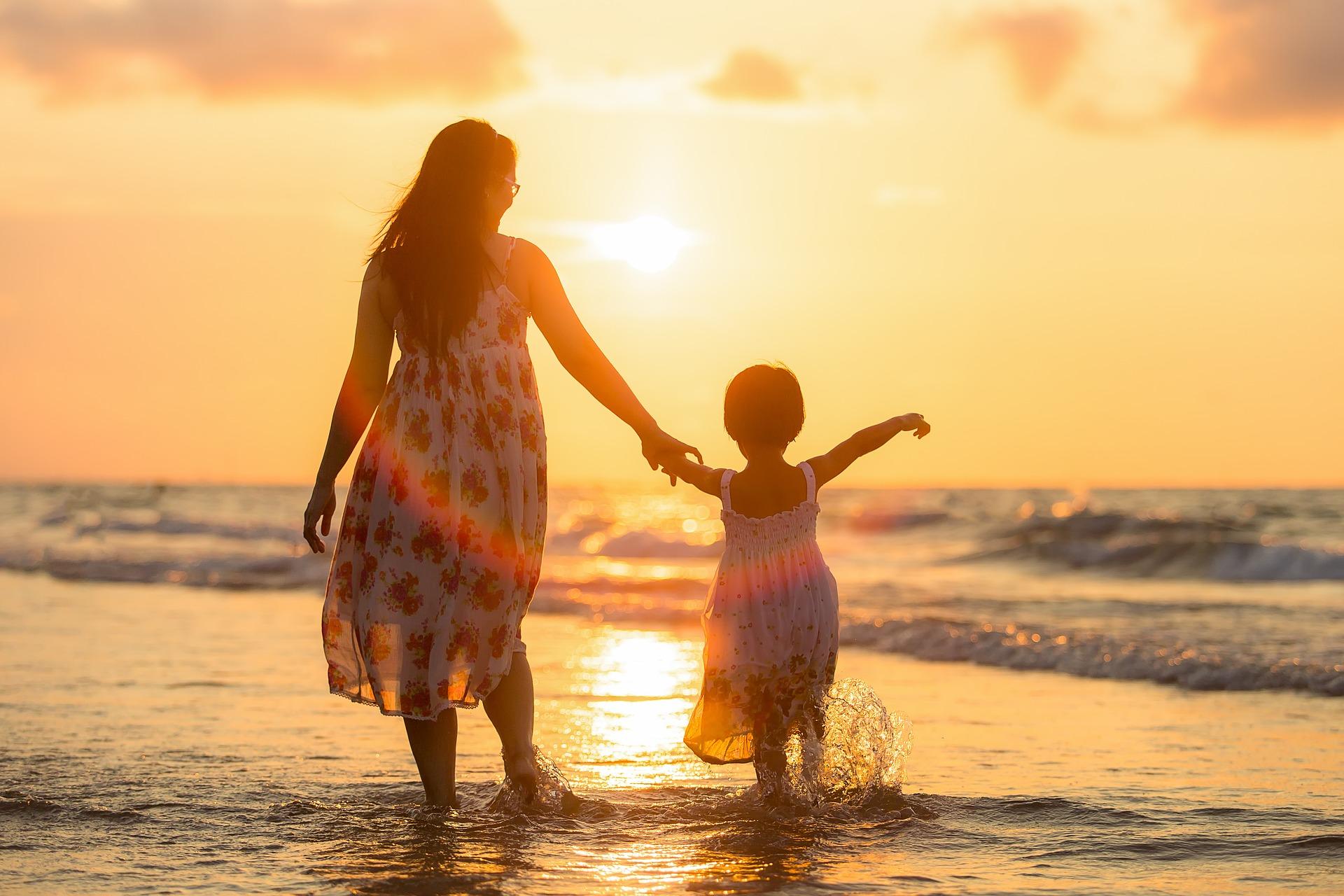 夕焼けの海を歩く大人と子供
