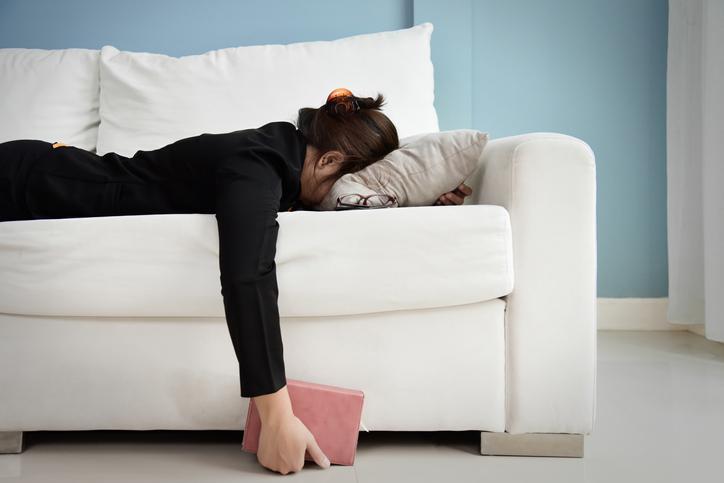 疲れてソファーで横になる女性