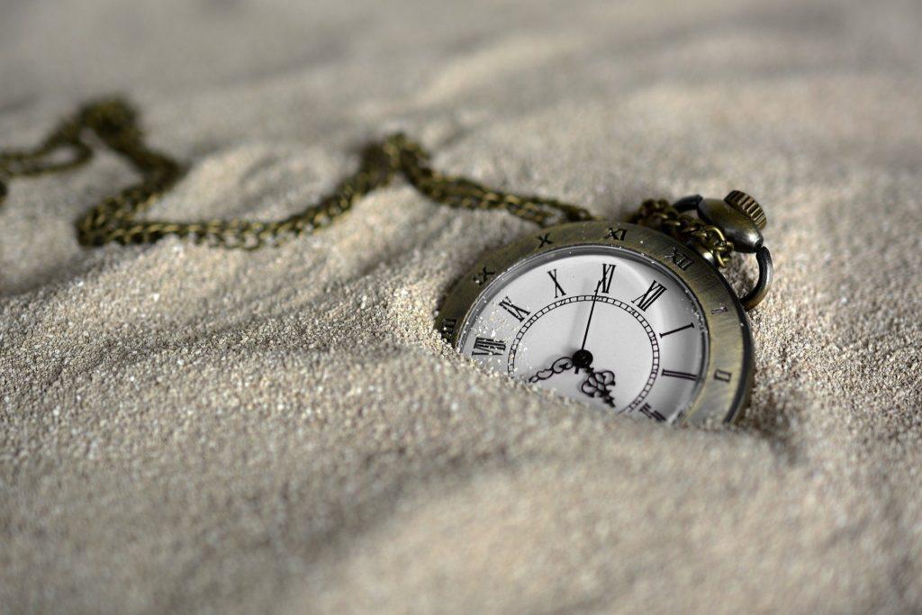 砂の中に埋まる時計