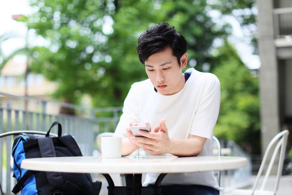 屋外のテーブルでスマートフォンを触る男性