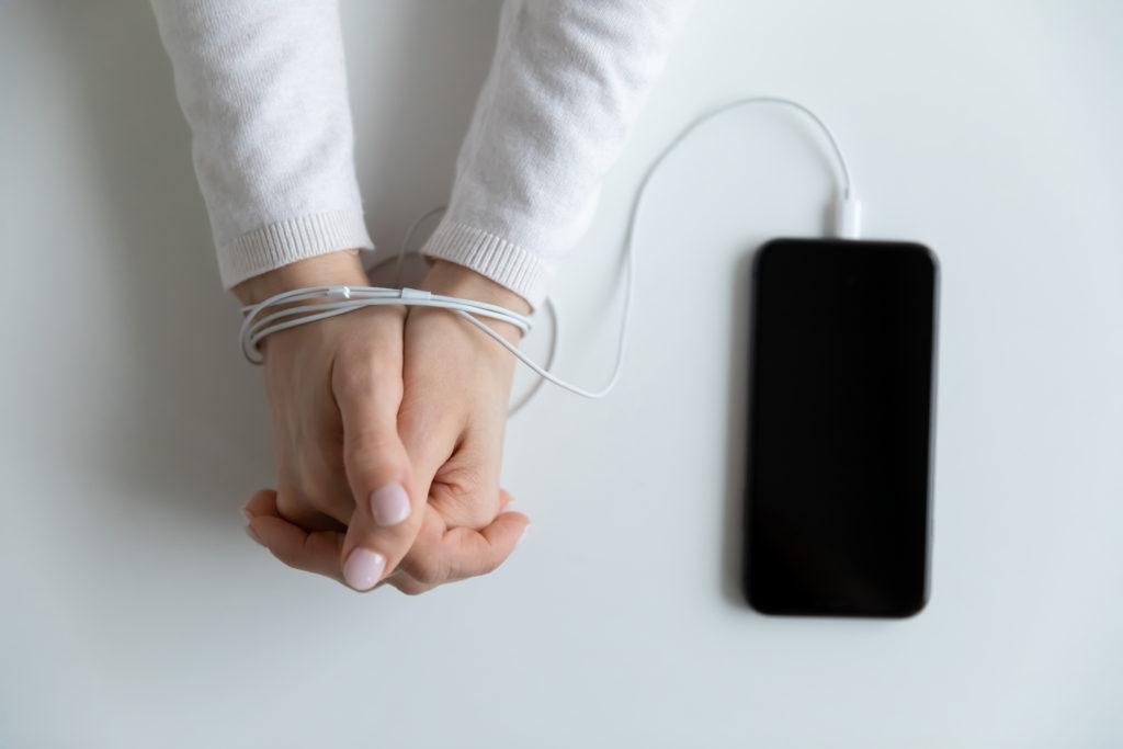 手首をスマートフォンのケーブルで縛られている人