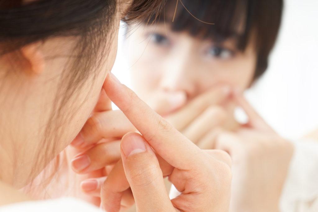 鏡を見て容姿を気にする女性