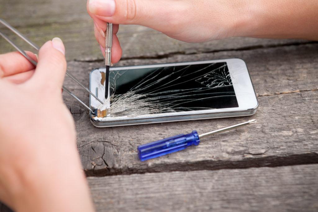 スマートフォンの割れた画面を修理する人